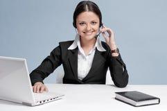 Affärskvinna med hörlurar med mikrofonkommunikation Arkivbilder