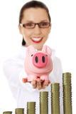 Affärskvinna med henne besparingar i en piggy grupp Arkivbilder