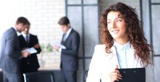 Affärskvinna med hennes personal, folkgrupp i bakgrund på det moderna ljusa kontoret inomhus royaltyfria foton