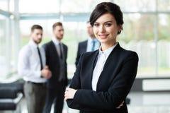Affärskvinna med hennes personal, folkgrupp i bakgrund på det moderna ljusa kontoret inomhus fotografering för bildbyråer