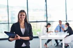Affärskvinna med hennes personal i bakgrund på kontoret Arkivfoton
