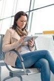 Affärskvinna med internetminnestavlan på flygplatsen Arkivfoton