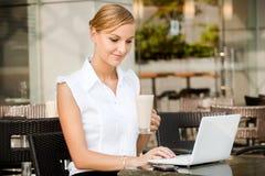 Affärskvinna med kaffe & bärbar dator Fotografering för Bildbyråer