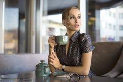 Affärskvinna med kaffe- eller tekoppen som bort ser Affärskvinna som ler och rymmer tekoppen på lunchavbrott, når möte Royaltyfria Foton