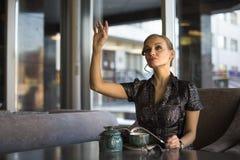 Affärskvinna med kaffe- eller tekoppen som bort ser Affärskvinna som ler och rymmer tekoppen på lunchavbrott, når möte Arkivfoto