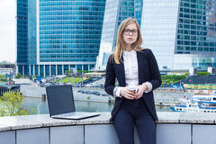 Affärskvinna med kaffe och en bärbar dator på bakgrunden av skyskrapor Arkivbild