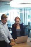 Affärskvinna med kollegan som arbetar på bärbara datorn på kontorsskrivbordet arkivbild