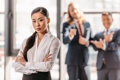 Affärskvinna med korsade armar, affärsmän som står behind, och att skratta Fotografering för Bildbyråer