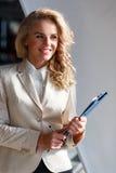 Affärskvinna med lockigt krabbt hår i inre kontor för stilfull dräkt Royaltyfria Bilder