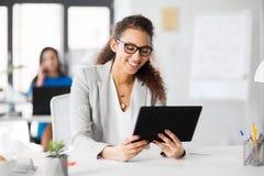 Affärskvinna med minnestavlaPC:n som arbetar på kontoret arkivfoto