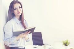 Affärskvinna med notepaden i solbelyst kontor royaltyfria foton