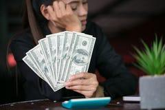 Affärskvinna med pengar i handen, händer som räknar oss dollarräkningar royaltyfria bilder