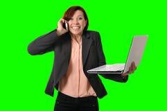 Affärskvinna med rött hår som talar på den hållande bärbara datorn för mobil mobiltelefon i handen som isoleras på grön skärmcrom Arkivbild