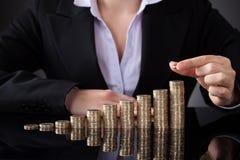 Affärskvinna med rad av mynt arkivfoton