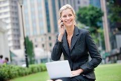 Affärskvinna med telefonen och bärbar dator Royaltyfria Bilder