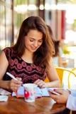 Affärskvinna med telefonen och notepaden som gör affär i kafé royaltyfri foto