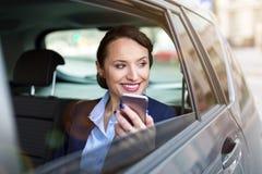 Affärskvinna med telefonen på baksätet av en bil royaltyfri foto