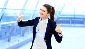Affärskvinna med tummar som ser upp lyckliga Royaltyfri Fotografi