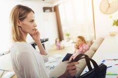 Affärskvinna Mom Talking Phone i vardagsrum royaltyfri foto