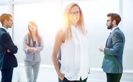Affärskvinna och hennes kollegor som står i kontoret arkivfoto