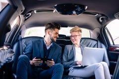 Affärskvinna och man på en backseat av limoen Arkivfoton