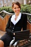 Affärskvinna på en bänk som ser ner gatan Royaltyfri Foto
