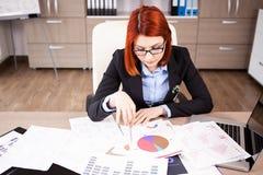 Affärskvinna på hennes skrivbord som arbetar på diagram och diagram Royaltyfri Bild