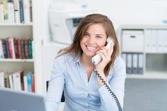 Affärskvinna på kontorsskrivbordet som talar på telefonen Arkivfoto