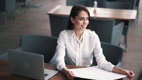 Affärskvinna på lunchtime i kafét som bort ser, bärbar dator på tabellen, ultrarapid stock video