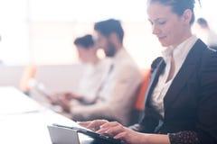 Affärskvinna på möte genom att använda minnestavlan Arkivfoton