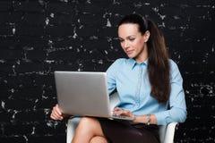 Affärskvinna på stol med bärbara datorn Arkivbild