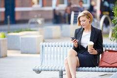 Affärskvinna On Park Bench med kaffe genom att använda mobiltelefonen Royaltyfria Bilder