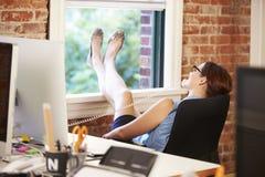 Affärskvinna On Phone Relaxing i modernt idérikt kontor arkivbild