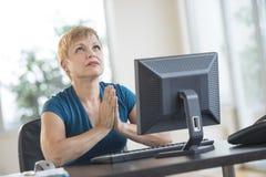 Affärskvinna Praying While Sitting på skrivbordet Fotografering för Bildbyråer