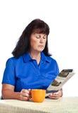 Affärskvinna Reading Paper And som dricker kaffe Arkivfoton