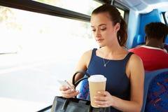 Affärskvinna Sending Text Message på bussen Fotografering för Bildbyråer