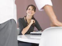 Affärskvinna Sitting At Desk som ser den manliga kollegan royaltyfria bilder