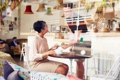 Affärskvinna som är betjänad av uppassare i en coffee shop Arkivfoto