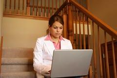 Affärskvinna som är funktionsduglig hemma på henne bärbar dator royaltyfri foto