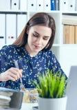 Affärskvinna som äter lunch på hennes arbetsplats som ser bärbar datorskärmen Mappar med dokument i förgrunden royaltyfria foton