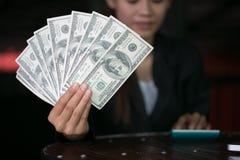 Affärskvinna som över visar en spridning av kassa och att spendera pengar eller vinst från begrepp för affärsoperationer arkivfoton