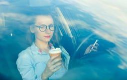 Affärskvinna som överför ett textmeddelande och dricker kaffe medan D arkivbild