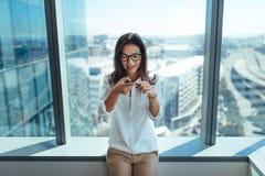 Affärskvinna som överför stämmameddelandet genom att använda mobiltelefonen Arkivbild