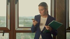 Affärskvinna som övervakar genom att använda mobiltelefonen i konstruktionsplats lager videofilmer