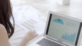 Affärskvinna som analyserar graf- och diagramfinans av marknadsföringen med information om data på minnestavla- och bärbar datord lager videofilmer