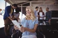 affärskvinna som använder den digitala minnestavlan med kollegor i bakgrund Royaltyfria Foton