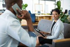 Affärskvinna som använder den digitala minnestavlan medan en kollega som talar på mobiltelefonen Royaltyfri Foto