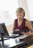 Affärskvinna som använder den digitala minnestavlan på skrivbordet Arkivbild