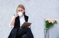 Affärskvinna som använder digitalt minnestavla- och drinkte, medan sitta på kafét, attraktivt kvinnligt block för freelancerinneh royaltyfri fotografi