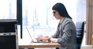 Affärskvinna som använder en bärbar dator i startup kontor royaltyfri fotografi